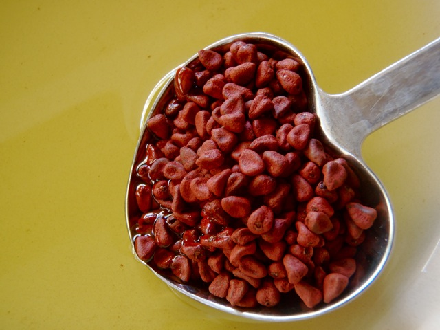 heart-shaped tablespoon filled with annatto seeds