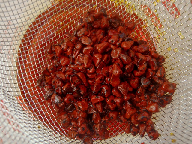 annato seeds in a strainer over the reddish oil