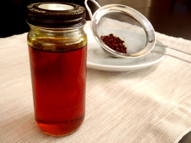 annatto seed oil in a small spice jar with strainer with the seeds behind it