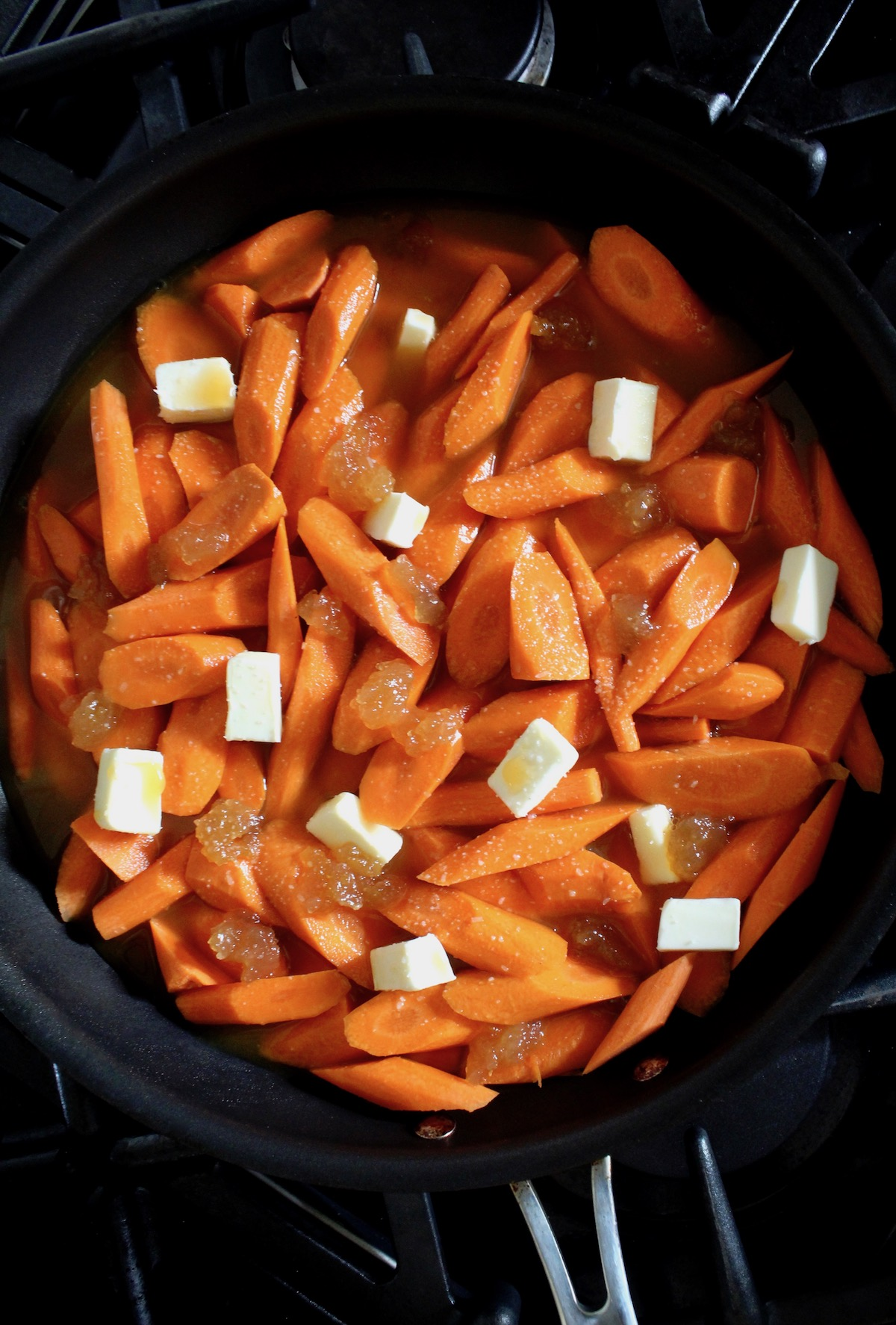 sliced carrots in saute pan with pieces of butter on top