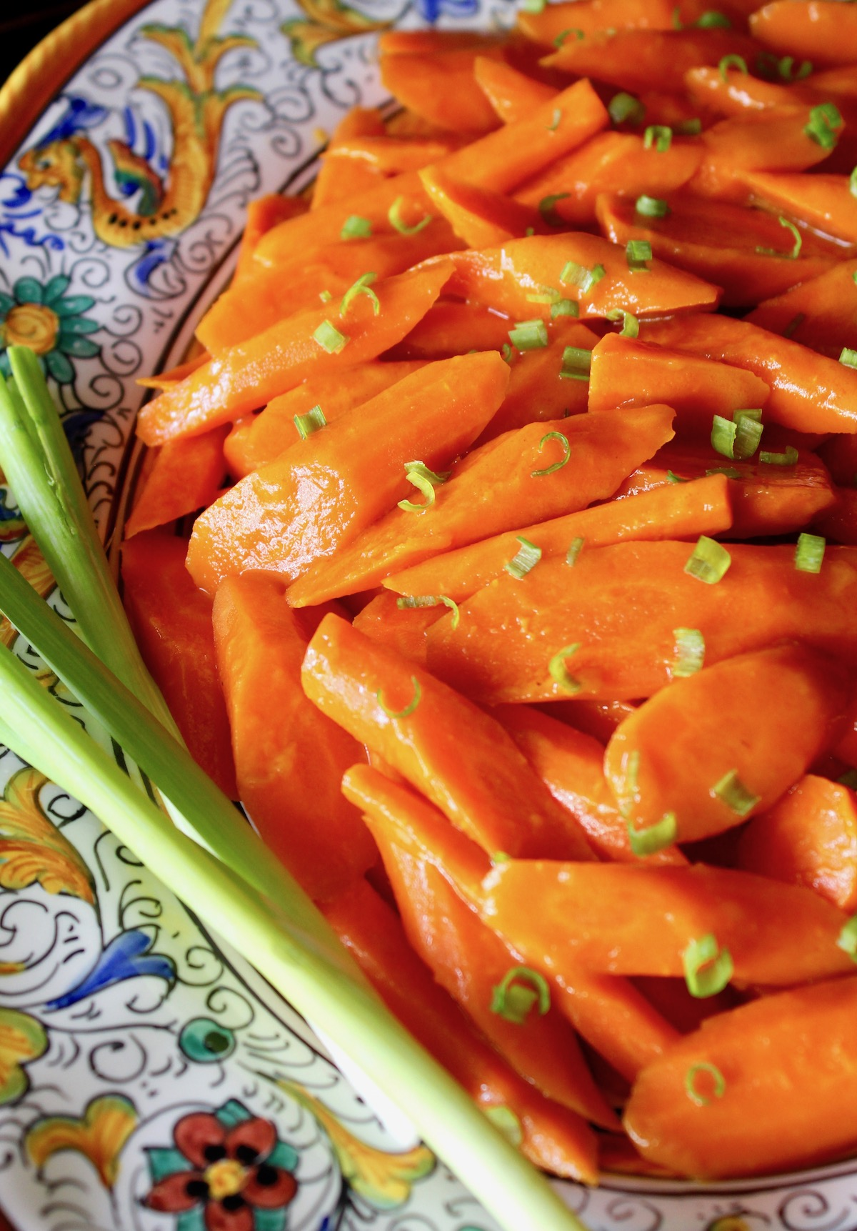 close up of apricot glazed carrots with chopped scallions