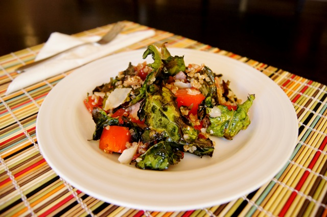 Kale Chip-Quinoa Salad With Pancetta and Tomato Vinaigrette on a white plate with a colorful bamboo placemat beneath it