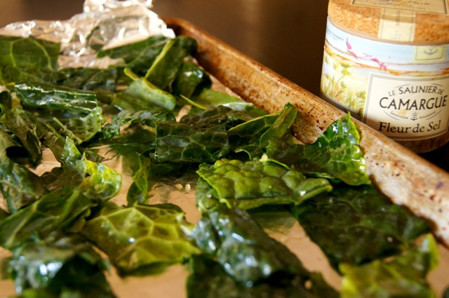 Roasted Kale chips on a baking sheet with a container of Fleur de Sel behind it