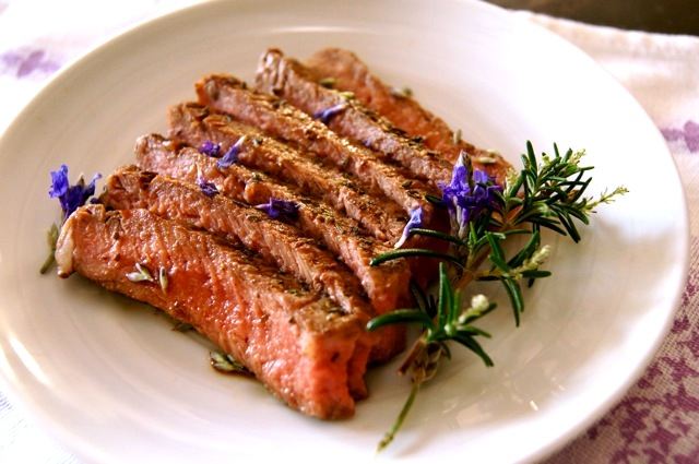 A few slices of Lavender Rosemary Grilled Ribeye Steak on a small white plate.