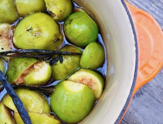 fresh green figs in water in an orange pot with vanilla beans