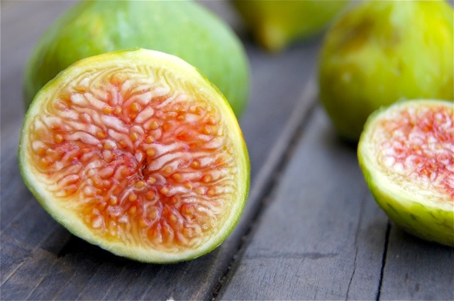 Fresh green figs sliced in half on wooden surface