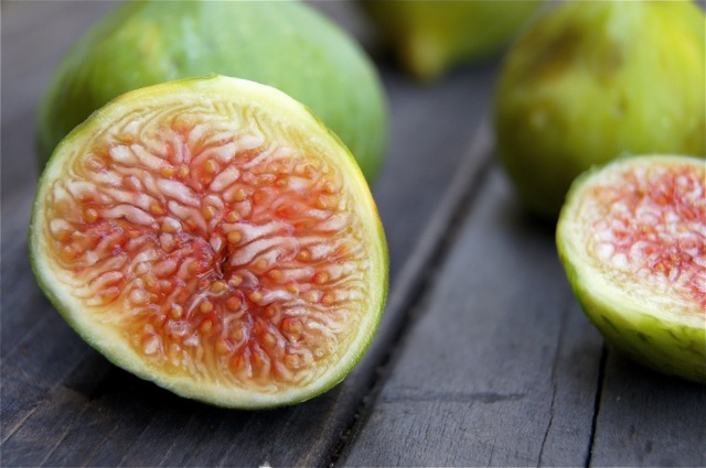 Green figs on a wooden table, with one sliced in half getting ready to be used in Vanilla Fig Preserves.