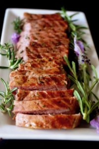Sliced Lavender-Rosemary Grilled Ribeye Steak on a narrow white platter, showing grill marks, with fresh herbs.