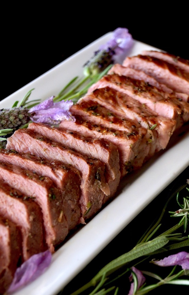 Sliced Lavender-Rosemary Grilled Ribeye Steak on a narrow white platter with fresh herbs.