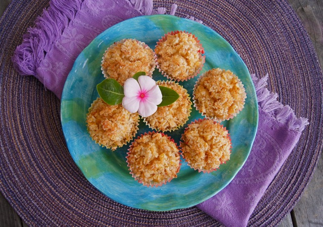 Several gluten-free Lemon Coconut Muffins on a bright blue-green plate with one pretty, pink Impatient flower.