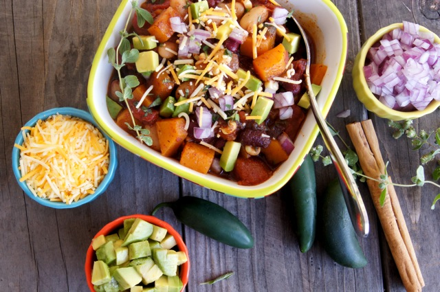 Top view of Roasted Butternut Squash Vegetarian Chili in a square bowl surrounded with condiments, cinnamon sticks and whole jalapeno peppers.