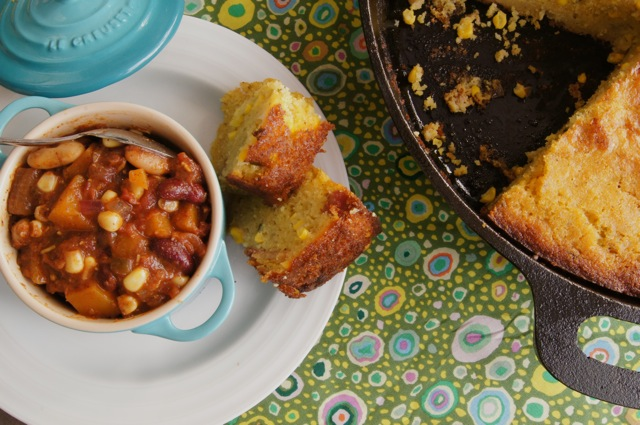 STop view of a couple of slices of Skillet Jalapeno-Bacon Cornbread on a white plate next to a bowl of chili.