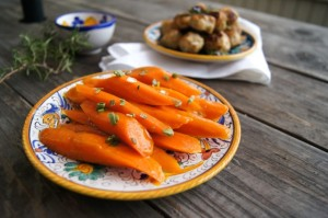APricot Glazed Carrots on gold-rimmed plate with a plate of meatballs in the background.
