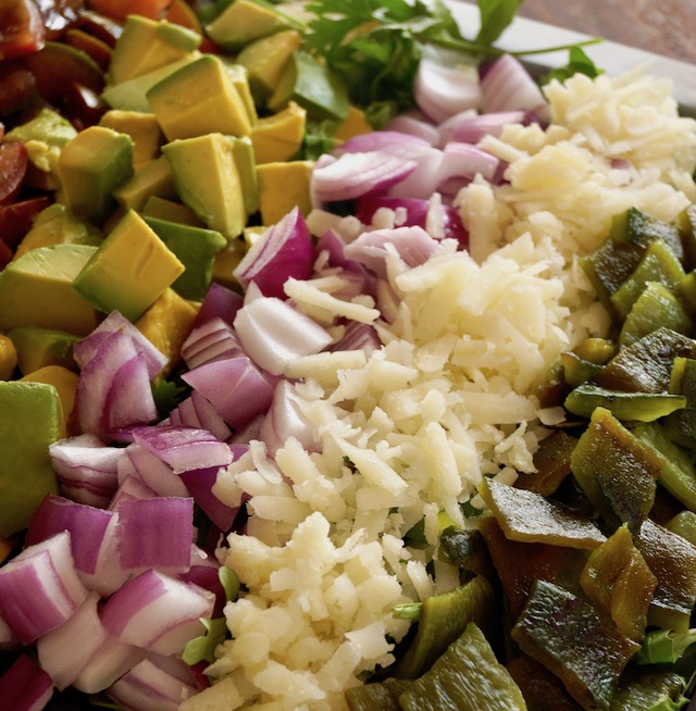 Rows of avocado, red onion, manchego cheese and roasted pobalnos for Mexican chopped salad with pepitas