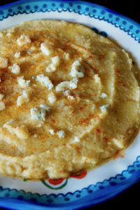 Blue-rimmed bowl with creamy gorgonzola polenta