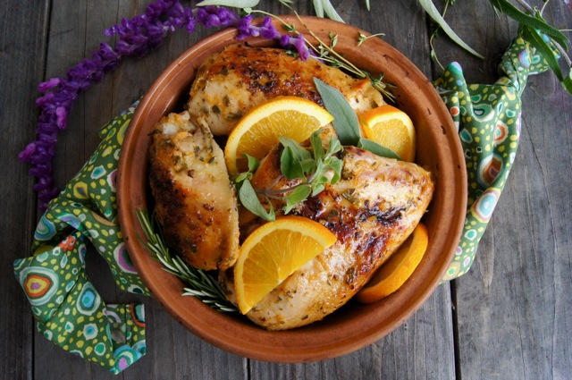 Herbs de Provence Orange Roasted Chicken recipe in a round teracotta dish with purple flowering Mexican sage.