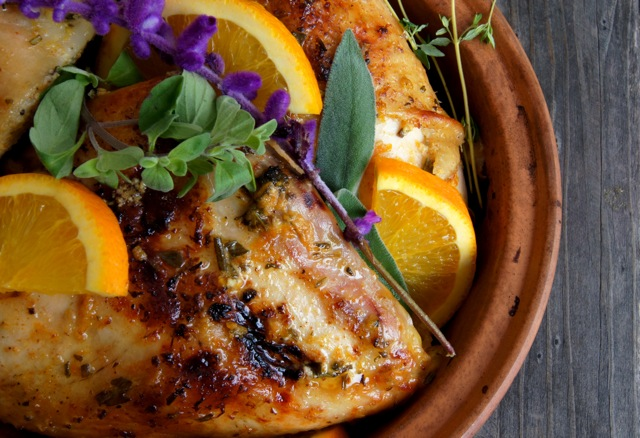 Close up of Herbs de Provence Orange Roasted Chicken recipe in teracotta dish with orange slices and fresh herbs.