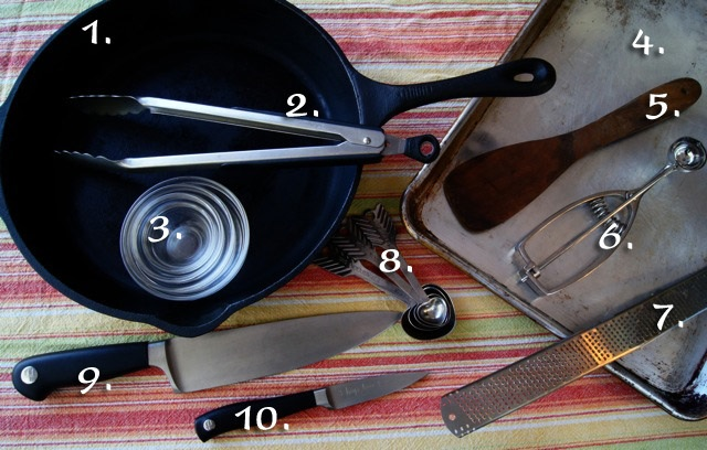 Skillet, tongs, bowls, knives, sheet pan, wooden spatula, cookie scoop and measuring spoons on a striped tablecloth.