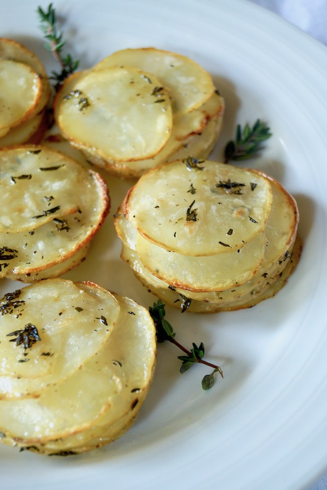 A few Pommes Anna on a white plate with fresh thyme