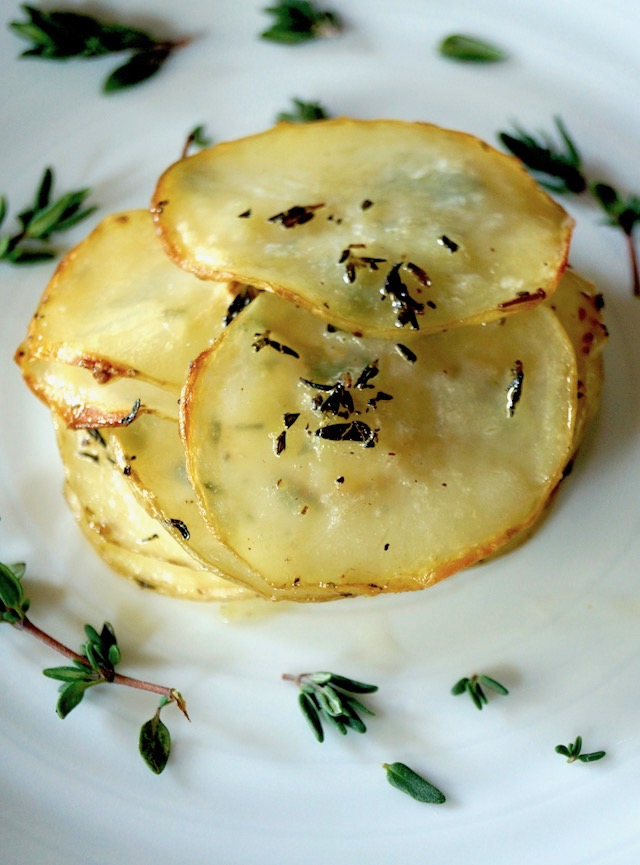 One Pommes Anna on a white plate with thyme