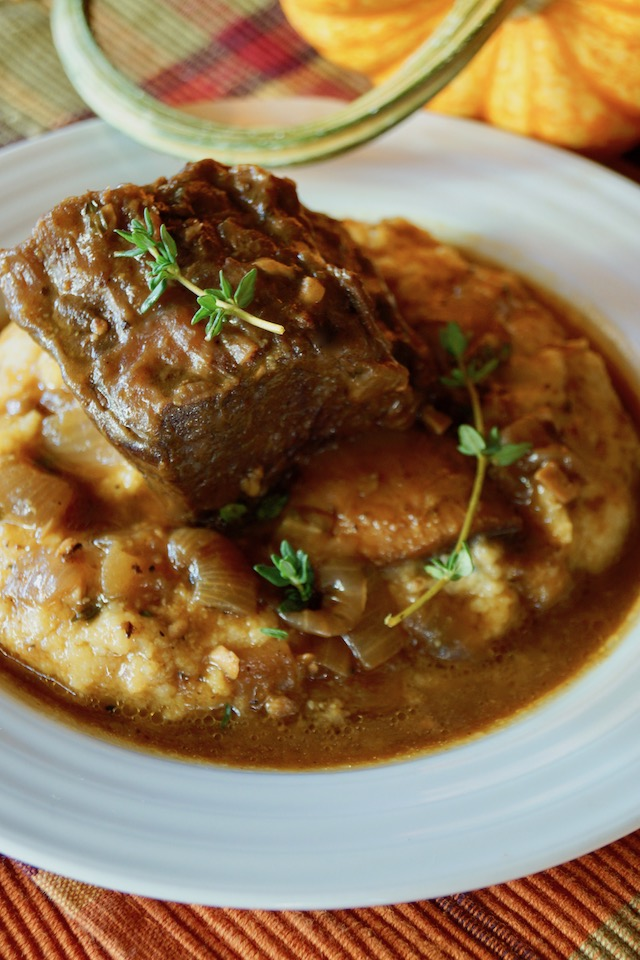 Serving of Pumpkin Braised Short Ribs on polenta with fresh thyme, in a white plate with pumpkin in background.