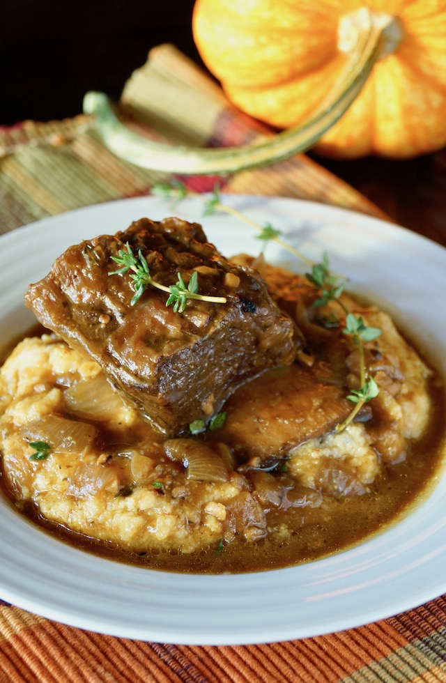 One serving of Pumpkin Braised Short Ribs on a bed of polenta with pumplin in background