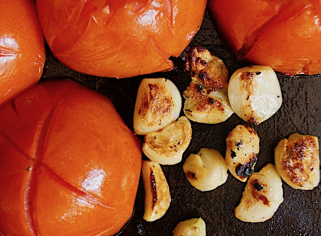 roasted garlic cloves and tomato halves on sheet pan