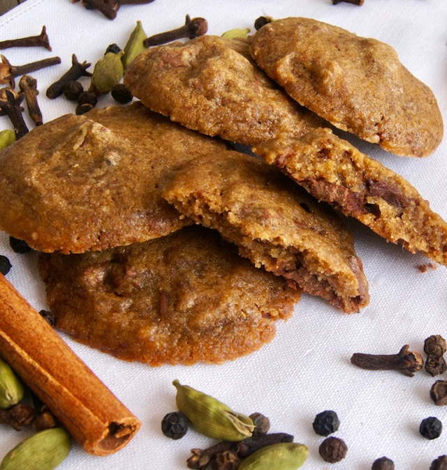 Several Chocolate Chai Cookies on a white cloths wiht whole spices around them.