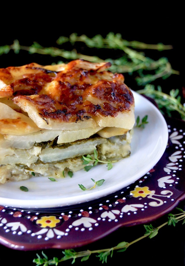 1 serving of Gruyere Spinach Potatoes Au Gratin on a white plate surround by fresh thyme sprigs.