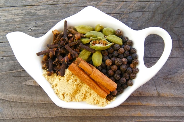Spices including cinnamon, peppercorns, cardamom, cloves and ginger in a white, tea pot shaped dish.