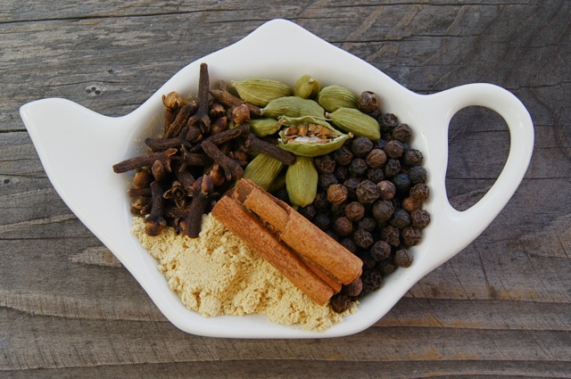 whole cloves, cinnamon, peppercorns and cardamom, with ground ginger, in a white tea kettle-shaped dish