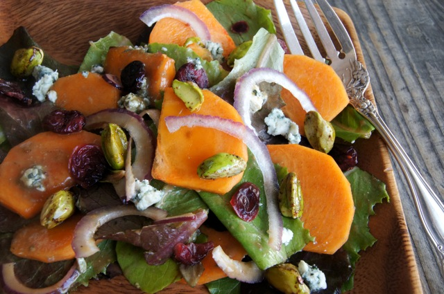 Persimmon Salad with Blue Cheese and Honey Glazed Pistachios on a square wooden plate
