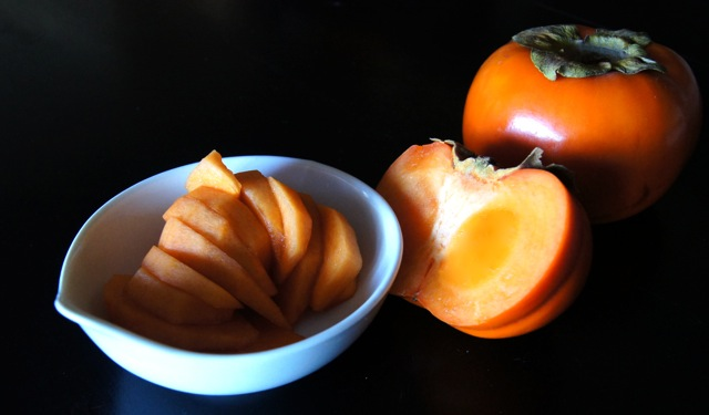 deep orange Fuyu persimmon, one whole and one sliced in white bowl