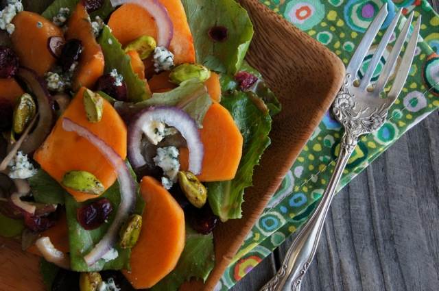 Winter Persimmon Salad with Blue Cheese on a square wooden plate