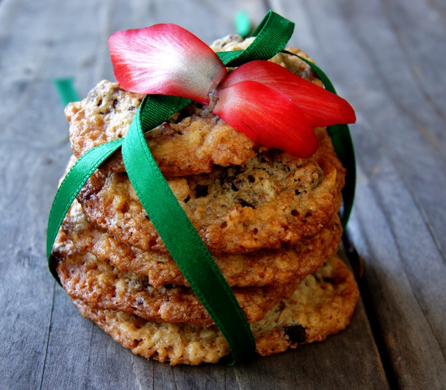 Gluten-Free Oatmeal Chocolate Cherry Lace Cookies with a green ribbon and petals from a red Christmas Cactus flower.