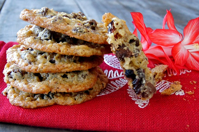 Small stack of Gluten-Free Oatmeal Chocolate Cherry Lace Cookies, with one broken in half.