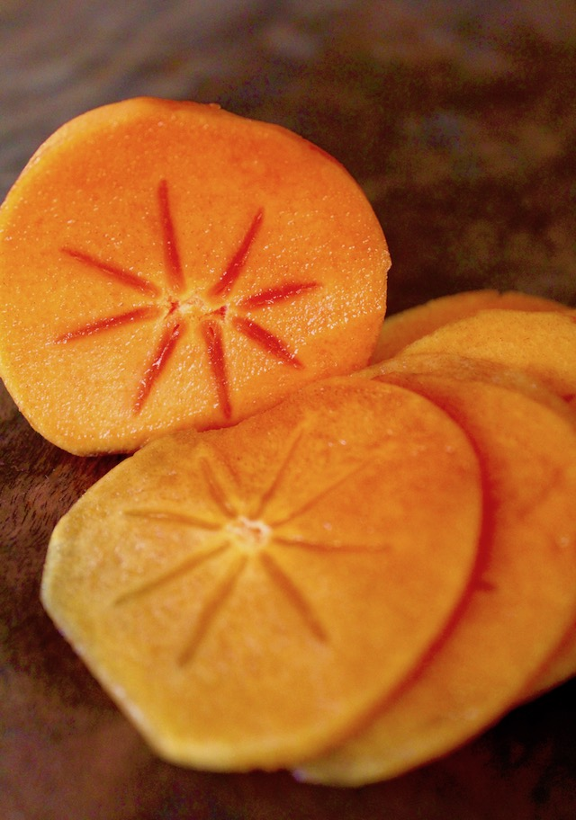 thinly sliced fuyu persimmon on woode cutting board