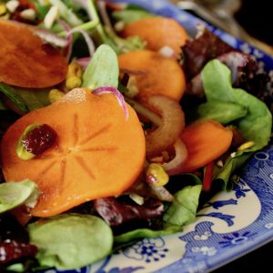 close up of Persimmon salad on blue and white china platter