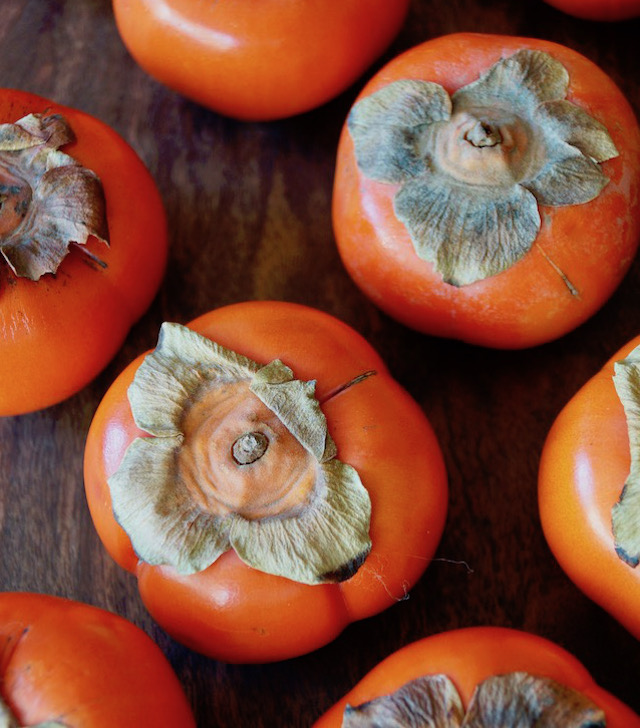 several fuyu persimmons on cutting board