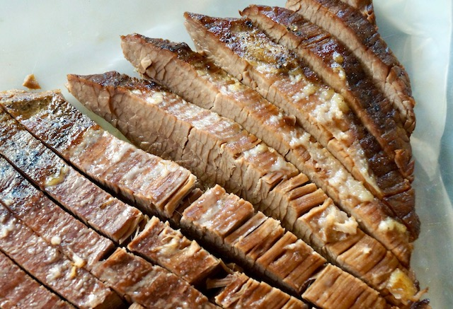 Sliced brisket on white parchment paper.