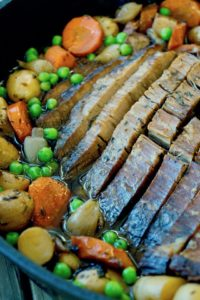 Close up of sliced brisket on a cast iron skillet surrounded by potatoes, peas and carrots.