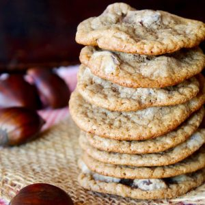 stack of Chestnut Cookies with chocolate chips on raw chestnuts next to them