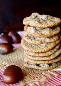 tall stack of Chestnut Cookies with chocolate chips on raw chestnuts next to them