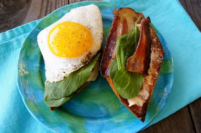 An open sandwich on a bright blue plate, with a sunny side egg on one half and bacon and spinach on the other.