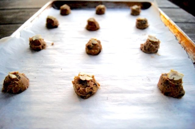 balls of chestnut cookie dough on a baking sheet with parchment paper