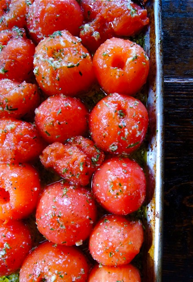 Peeled, halved tomatoes with rosemary on a sheet pan