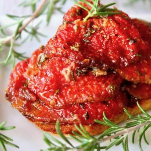 tomato confit with fresh rosemary on toast on white plate