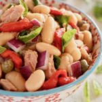 Close up of Cannelllini Bean Tuan Salad i a white bowl with blue trim and red flowers on it.