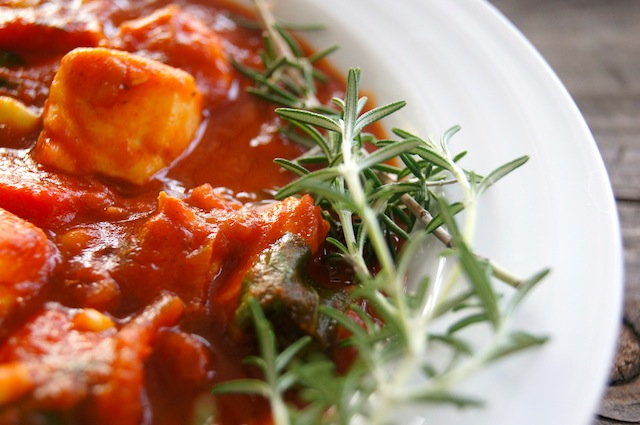 Smoky Tomato Fish Stew in white bowl with fresh rosemary sprigs