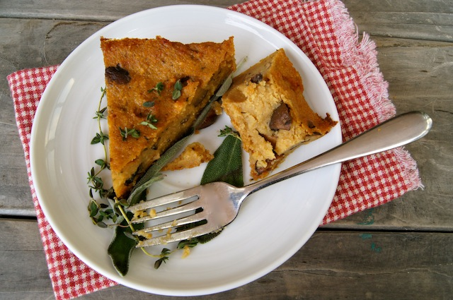 1 1/2 slices of Savory Polenta Cake with Mushrooms on a white plate with fresh herbs and a fork.